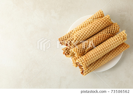 Plate with wafer rolls with condensed milk on white textured background 73586562