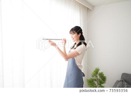 一個女人用措施測量窗簾的尺寸 73593356