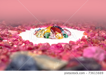 colorful diamonds surrounded by raw pink gemstones. 73613889