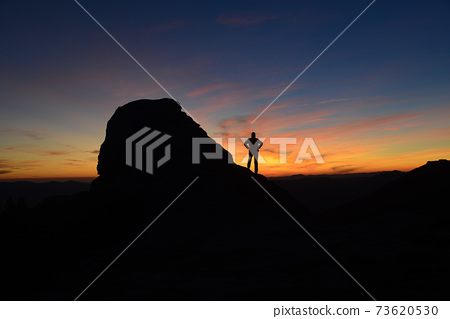 Man silhouette in mountains against sunrise background 73620530