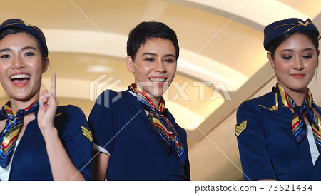 Cabin crew dancing with joy in airplane 73621434
