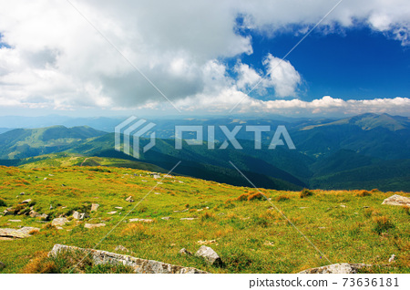carpathian summer mountain landscape. beautiful countryside with rocks on the grassy hill. view in to the distant valley. clouds on the blue sky. wonderful travel destination 73636181