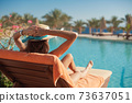 Woman in a straw hat relaxing on a daybed near a luxurious summer pool hotel Egypt, concept time to travel 73637051