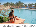 Woman in a straw hat relaxing on a daybed near a luxurious summer pool hotel Egypt, concept time to travel 73637055