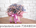 A bouquet of delicate small flowers in a box with a note. 73648034