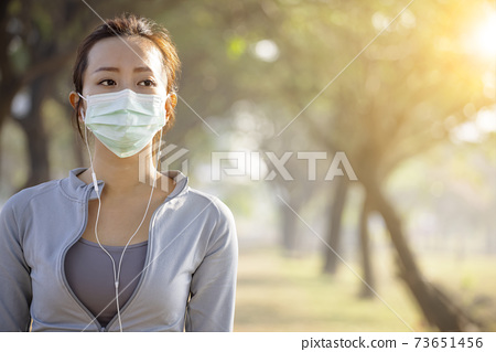 young woman in face mask and jogging in the park 73651456