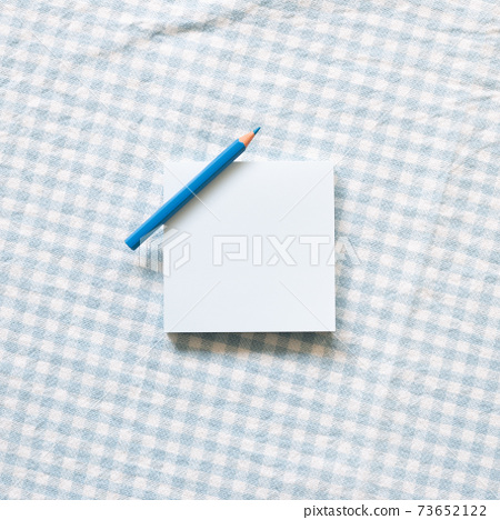 Blue memo pad with colored pencil on blue check pattern fabric background. top view, copy space 73652122