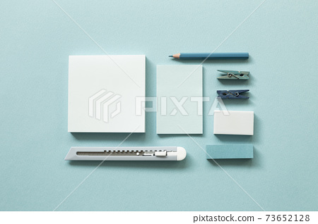 Blue stationery. Notepad, cutter, colored pencil, clip, eraser on blue background. flat lay, top view, copy space. Work and study place 73652128