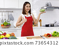 Happy Asian woman chef in red apron holding bowl of sunflower sprout in kitchen. 73654312