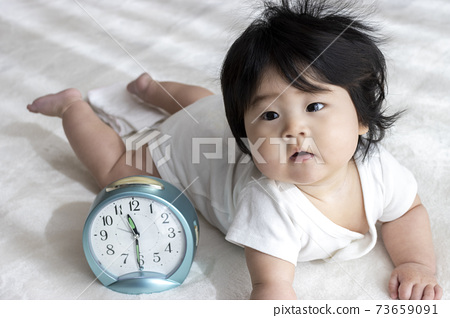 Baby and clock, childcare image (0 years old, 6 months old, girl, Japanese) 73659091