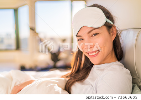 Happy Asian woman waking up early morning from beauty sleep wearing eye sleeping mask for a good night rest. Smiing young girl in bed 73663605