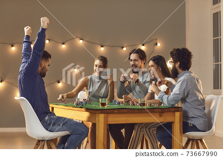 Young happy friends playing board games on table at home and having fun 73667990
