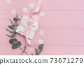 Valentines day or wedding gift, eucalyptus leaves frame paper hearts confetti and wooden pink background, empty space for your text, top view flat lay 73671279
