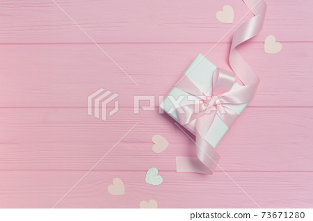 Gift box with ribbon on pink wooden background with place for your text. Mock up on Valentines Day, mothers day or Birthday. Top view, flat lay 73671280