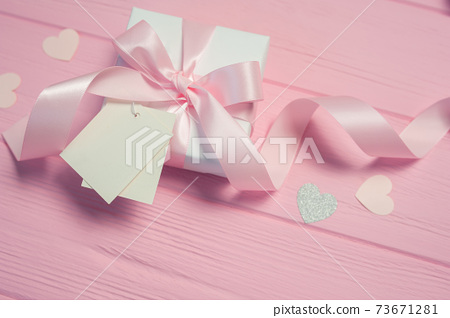 White gift box with a pink satin bow and ribbon on pink wooden background. Wedding mockup tag is included for your text. Can use for Valentines Day, mothers day, birthday 73671281