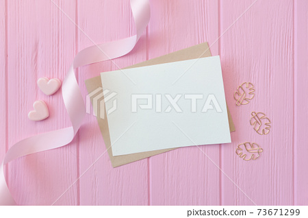 Wedding or birthday mock up scene. Blank open envelope with place for text for greeting card copyspace. Valentines card with two hearts on pink background. Flat lay, top view 73671299
