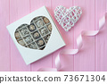 Chocolate handmade candies on pink wooden table. Chocolate box with heart and a festive ribbon. Gift for valentine's day 73671304