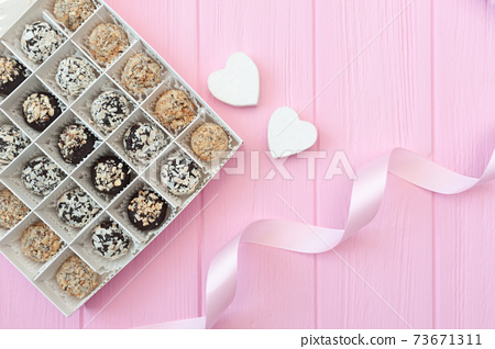 Chocolate handmade candies on pink wooden table. Chocolate box open with two hearts and a festive ribbon. Gift for valentine's day 73671311