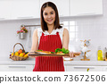 Asian woman chef in red apron holding salmon steak, serving on wooden board. Concept woman preparing meals at home. 73672506
