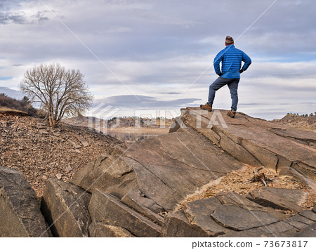 male hiker on a rocky cliff  at foothills of Rocky Mountains 73673817