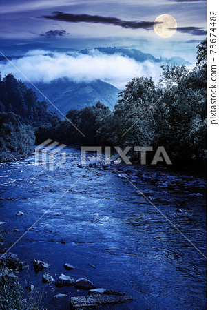 mountain river landscape in summer. wonderful nature scenery on foggy night. clouds rolling over the distant hill in full moon light. trees along the stream in the valley. weather with blue sky 73674482