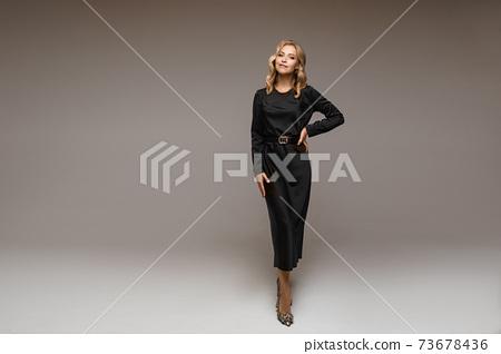 Beautiful blonde woman in black dress and heels. 73678436