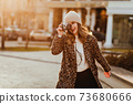 Positive european woman in coat posing with camera 73680666