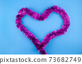 Valentines Day concept Purple Shiny Tinsel Garland in heart form shape for Holiday Decoration on blue Background 73682749