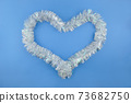 Christmas Slver Shiny Tinsel Garland in heart form shape for Holiday Valentine Decoration on blue Background 73682750