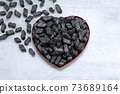 Cardbox in form of heart with black  Packing peanuts  bubbly plastic protective granules Styrofoam chips Background. love or valentine day concept 73689164