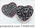 Cardbox in form of heart with black  Packing peanuts  bubbly plastic protective granules Styrofoam chips Background. love or valentine day concept 73689165