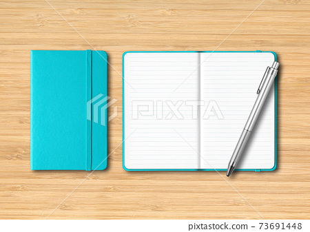 Aqua blue closed and open lined notebooks with a pen on wooden background 73691448