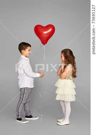 couple of little girl and boy with red heart balloons 73695127
