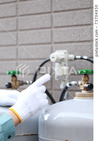 Workers inspecting propane gas cylinders 73704930