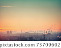 Silhouette sunrise, industry Europe town with haze factory, warehouse, building under colorful sky 73709602