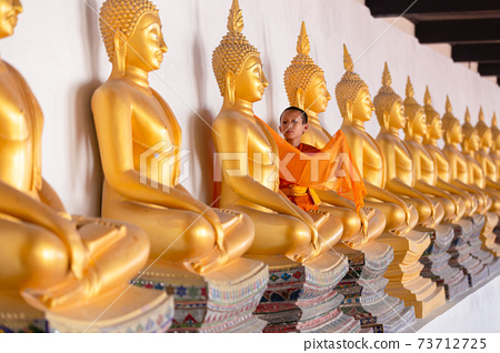 Asian young novice monk are covering cloth Buddha statue in Wat Phutthai Sawan Temple, Ayutthaya, Thailand 73712725
