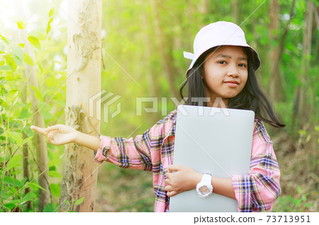 The little Asian girl holding tablet at the tropical farm, Little famer smile with happiness 73713951