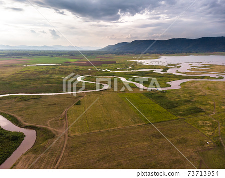 Scenic landscape aerial view of field river and basin against a natural mountain, Drone shot tropical landscape with noise and grain processed 73713954