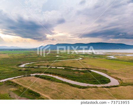 Scenic landscape aerial view of field river and basin against a natural mountain, Drone shot tropical landscape with noise and grain processed 73713955
