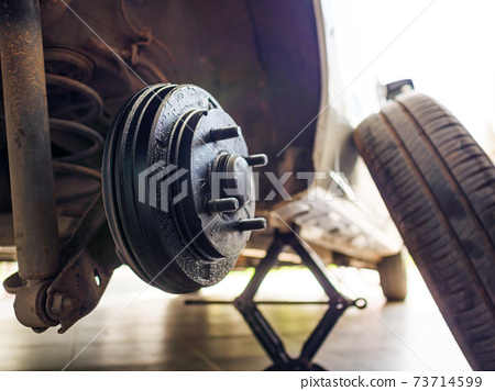 A rear hub of the car after removing a tire and wheel, maintaining a brake and wheel system, car jack-up for change a car wheel, Close-up shot 73714599