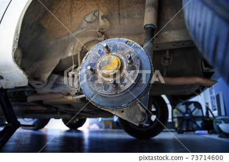 A rear hub of the car after removing a tire and wheel, maintaining a brake and wheel system, car jack-up for change a car wheel, Close-up shot 73714600
