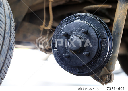 A rear hub of the car after removing a tire and wheel, maintaining a brake and wheel system, car jack-up for change a car wheel, Close-up shot 73714601