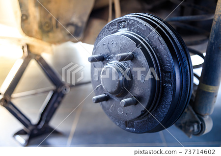 A rear hub of the car after removing a tire and wheel, maintaining a brake and wheel system, car jack-up for change a car wheel, Close-up shot 73714602