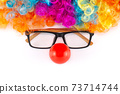 Funny Party concept face formed. Rainbow Clown Wig Set with glasses and red clown nose like a face, Fluffy Afro Synthetic Cosplay Anime Fancy Wigs Festive Background  73714744