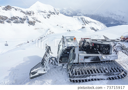 now-grooming machine on snow hill ready for skiing slope preparations in Swiss Alps. 73715917