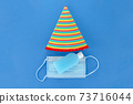 Vertical Top view of hand sanitizer gel bottle and face medical mask on Birthday Party concept on blue bg for prevention and health protection during flu virus Disease covid-19  73716044