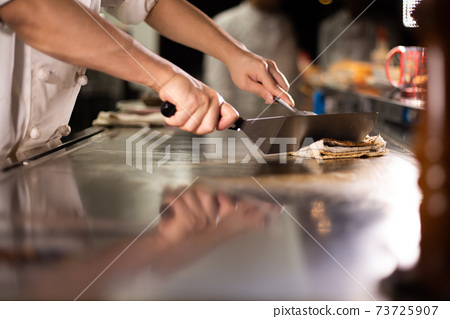 Cook cleaning the iron plate 73725907