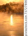 The orange sun shines reflecting off the ice of the river in the winter morning. 73727806