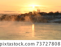 The orange sun shines reflecting off the ice of the river in the winter morning. 73727808