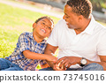 African American Father and Mixed Race Son Playing with Baseball in the Park 73745016